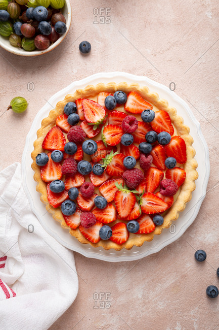 Overhead view of summer pie with berries on pink surface