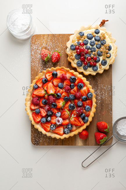 Strawberry and blueberry summer pies on cutting board