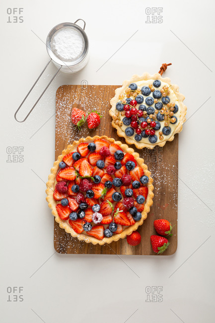 Strawberry and blueberry summer pies with powdered sugar on white background