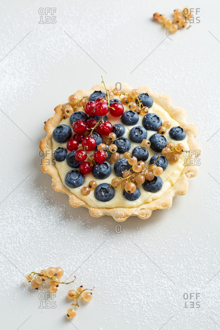 Close up of a blueberry tart on white stone surface