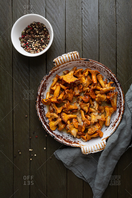 Chanterelle mushrooms roasted with butter in a rustic dish top view