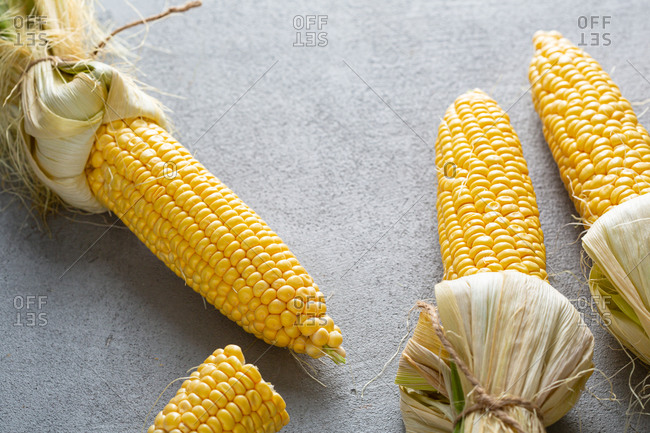 Close up of fresh corn on the cob on gray surface