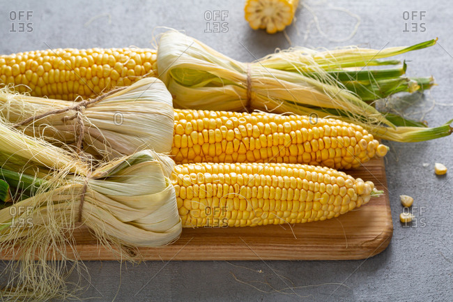 Close up of fresh corn on the cob on kitchen board