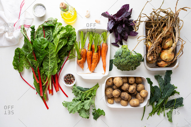 Overhead view of organic vegetables on white surface