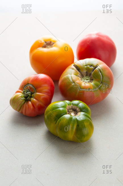 Fresh heirloom tomatoes on white surface