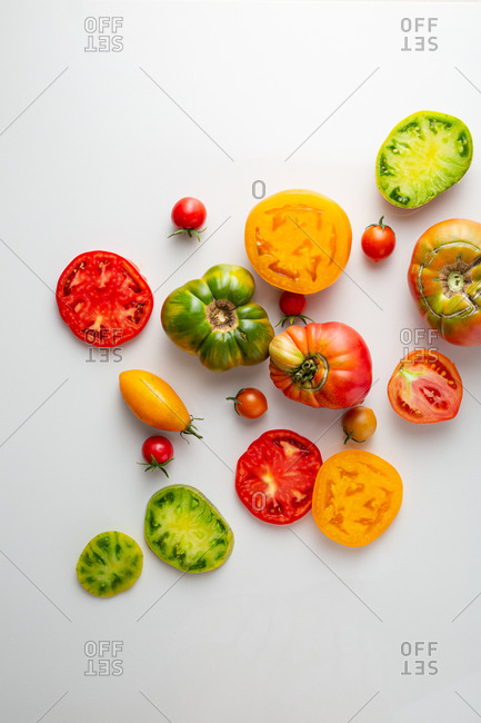 Overhead view of whole and sliced heirloom tomatoes on light surface