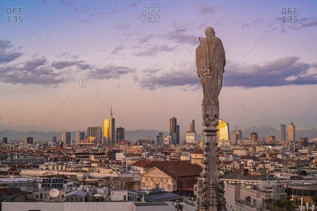 Italy, Lombardy, Milan - January 19, 2018: View of the statues on the Cathedral of Milan and the skyline of Milan seen on the background