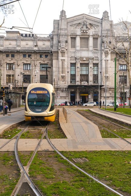Italy, Lombardy, Milan - January 20, 2018: A tram departing from central station with the  main station in the background