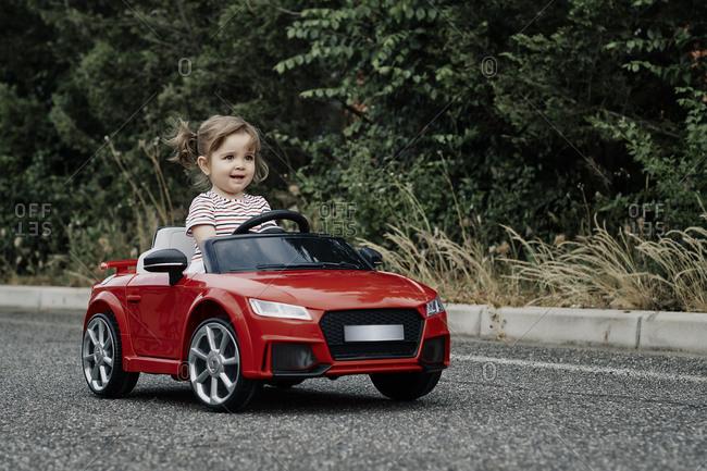 A girl riding a toy car