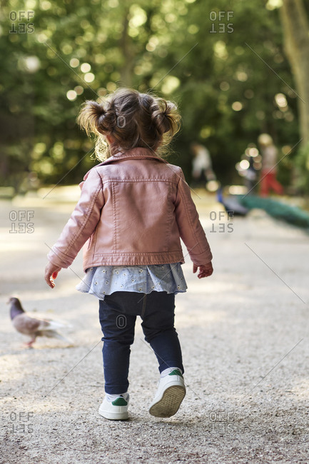 An 18 month old girl chasing a pigeon in a park