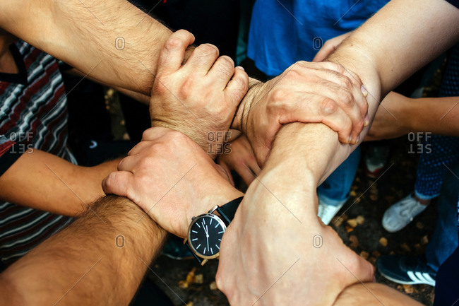 Men`s hands are woven together