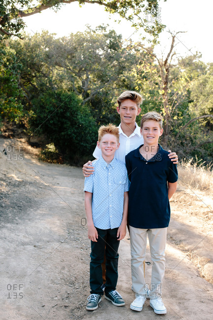 Three Brothers Smile Outside In Nature Smile For The Camera