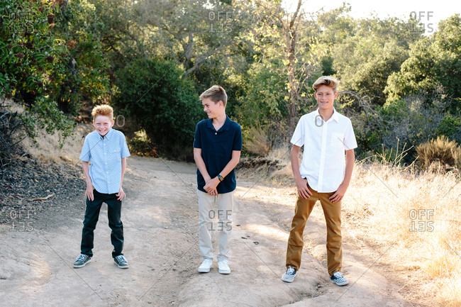 Three Young Brothers Stand Together Outside On a Trail Smiling