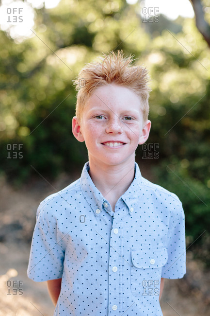 A Cute Red Haired Boy With Freckles Smiles For A Portrait Outside