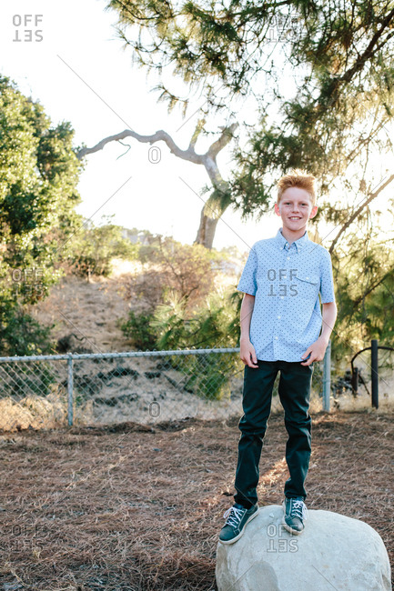 A Red Haired Boy Smiles While Standing On A Large Rock