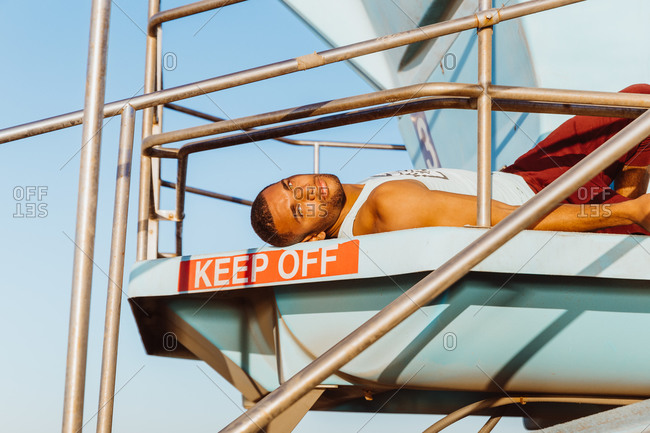 portrait of male athlete relaxing on lifeguard tower