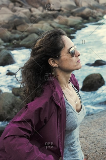 Beautiful woman contemplating the ocean with purple rain coat