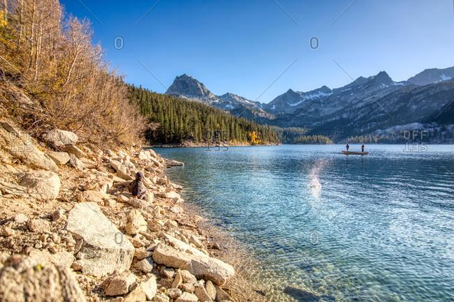 Little boy skipping rocks at lake while 2 men go fishing