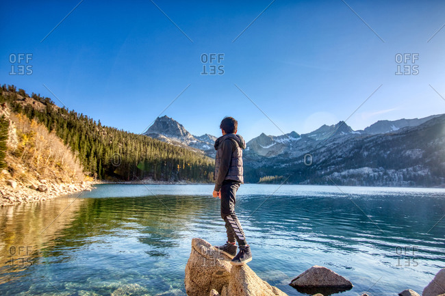 Boy looking over a lake in the Sierras, California.