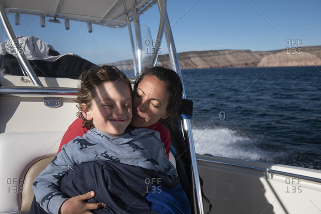 A mom and her son cuddling on a sailing boat at Espiritu Santo Island.