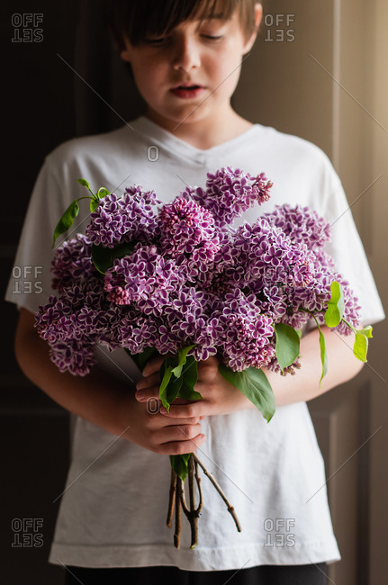 Image of a young boy holding a bouquet of purple lilac flowers.