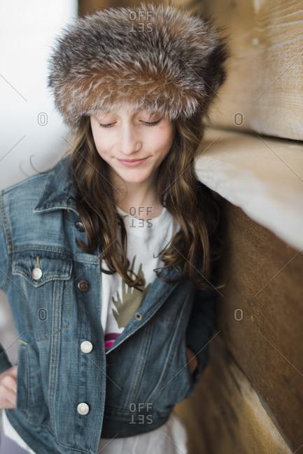 Girl in fur headband looking down