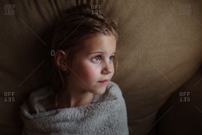 Little girl wrapped in towel after a bath looking away