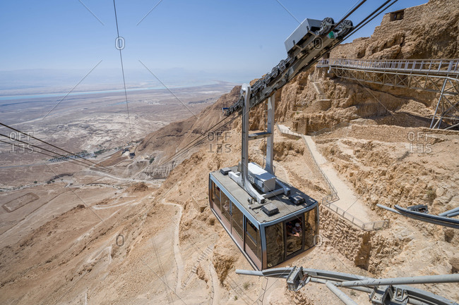Masada, North District, Israel - June 21, 2018: Yellow cableway start descent from masada fortress on sunny day israel