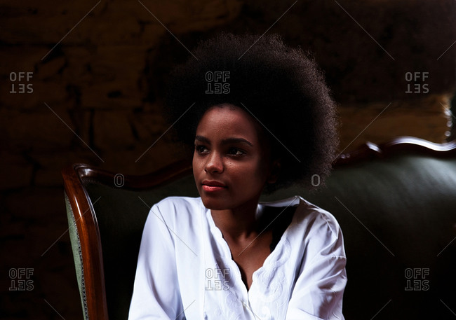 Black woman resting on green velvet sofa