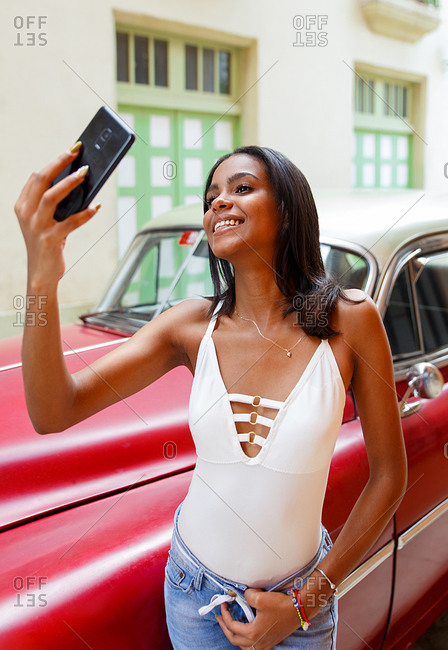 Young Cuban taking a selfie in front of an old car in Havana, Cuba