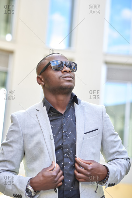 Stylish African American businessman posing with sunglasses.
