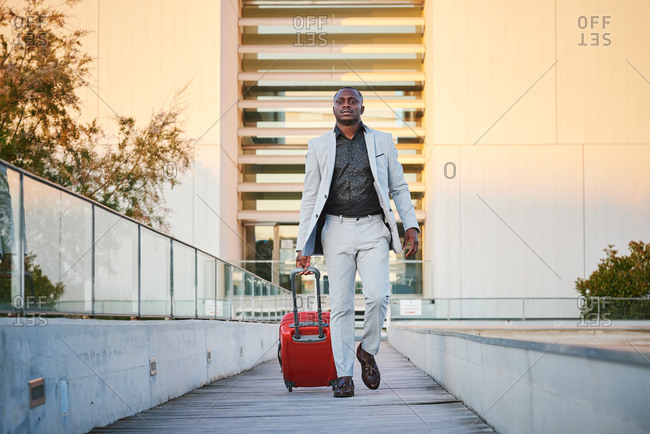 African-American man in a stylish suit and a red suitcase walking down a wooden walkway at sunset