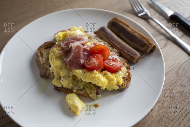 Close up of fresh scrambled eggs on toast with tomato and sausages