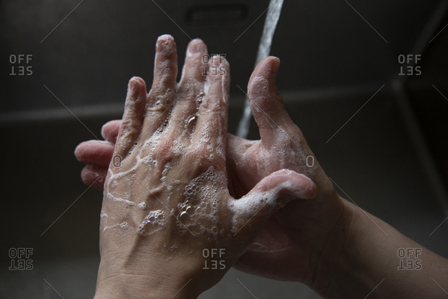 Close up of someone scrubbing their hands with soap in the sink