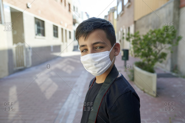 Boy with beautiful green eyes wearing a mask on the street