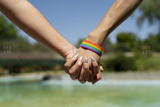 united hands of woman with LGBT bracelet
