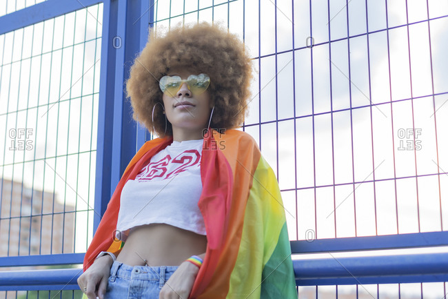 Woman with afro hair with her gay pride flag on her shoulders