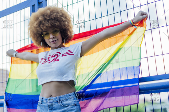 Woman holding her gay pride flag on a bridge
