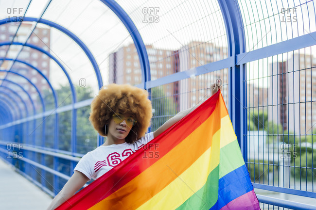 Proud woman with her gay pride flag on a bridge