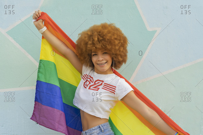 Woman with afro hair with gay pride flag