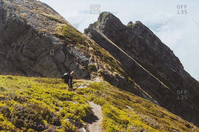 Young male with backpack hikes descending mountain ridge, Cantabria.