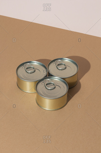 Set of tins with canned food on brown surface