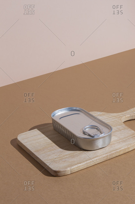 High angle of metal tin with preserved food on wooden cutting board