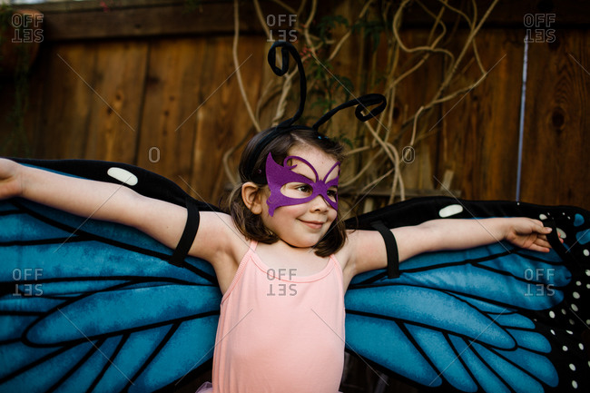 Young girl in dress up spreading butterfly wings
