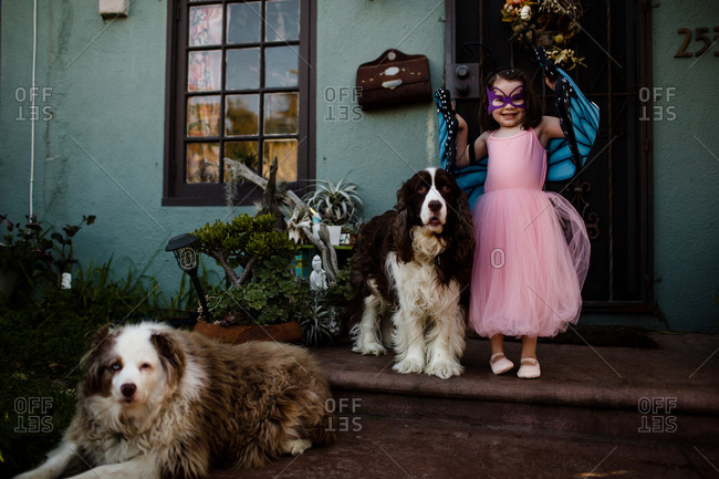 Young girl in dress up standing on porch with dogs
