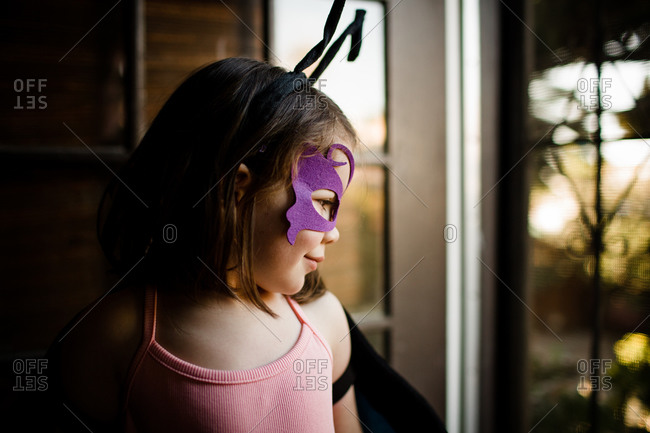 Young girl in dress up looking out front door