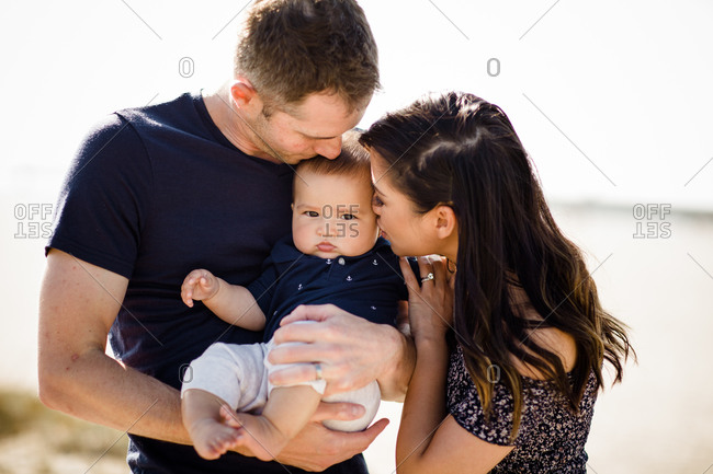 Mother & Father Kiss Infant Son on Beach