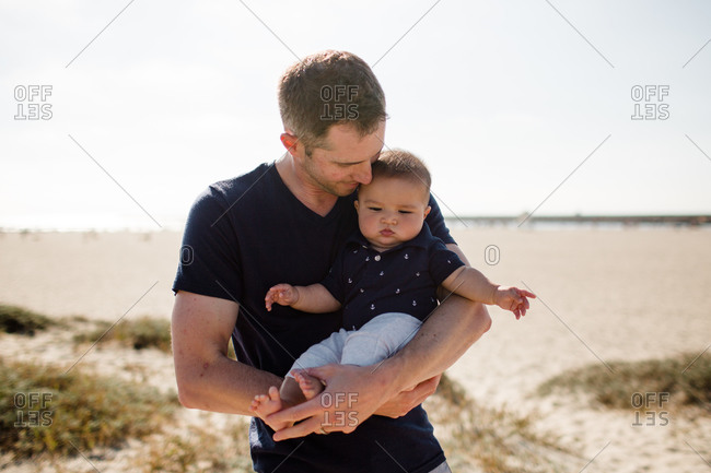 Father Cradling Infant Son on Beach