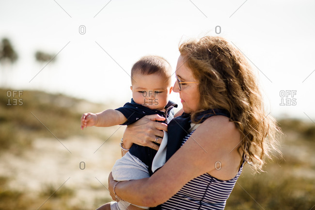 Grandmother Holding & Snuggling Grandson While Standing on Beach