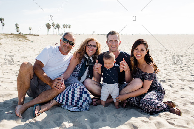 Family of Five Sitting on Beach Smiling for Camera